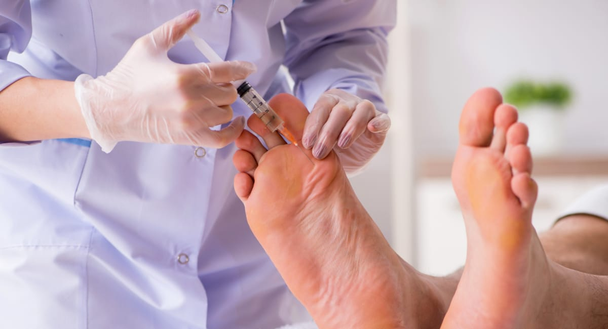Podiatrist performing injection therapy on foot